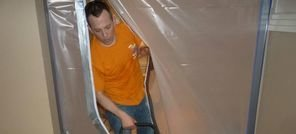 Water Damage Technician Using Air Mover Near Vapor Barrier